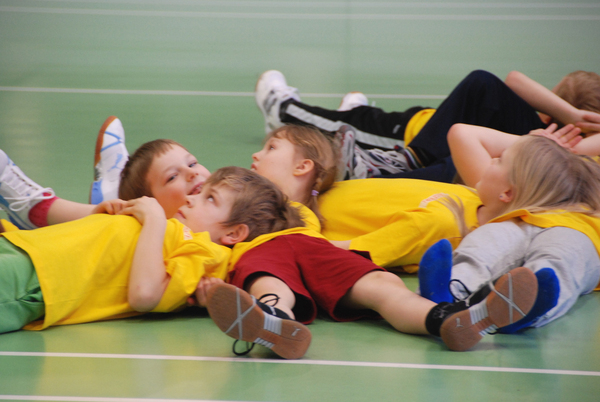 Lapset makaavat pelikentällä urheilusuorituksen jälkeen