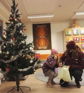 Lapsi ottaa lahjan joulukuusen alta