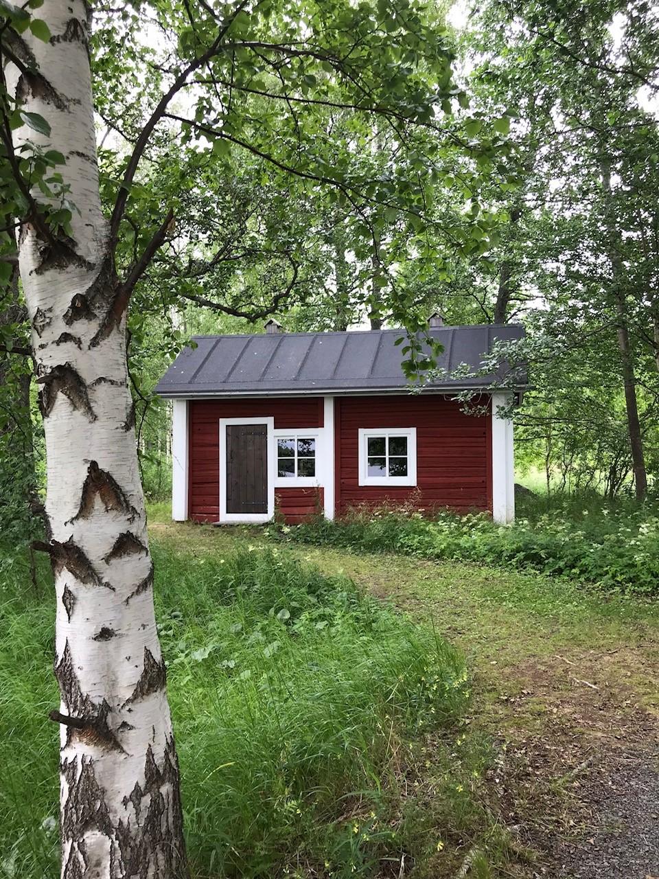 pieni punainen aittarakennus metsikössä