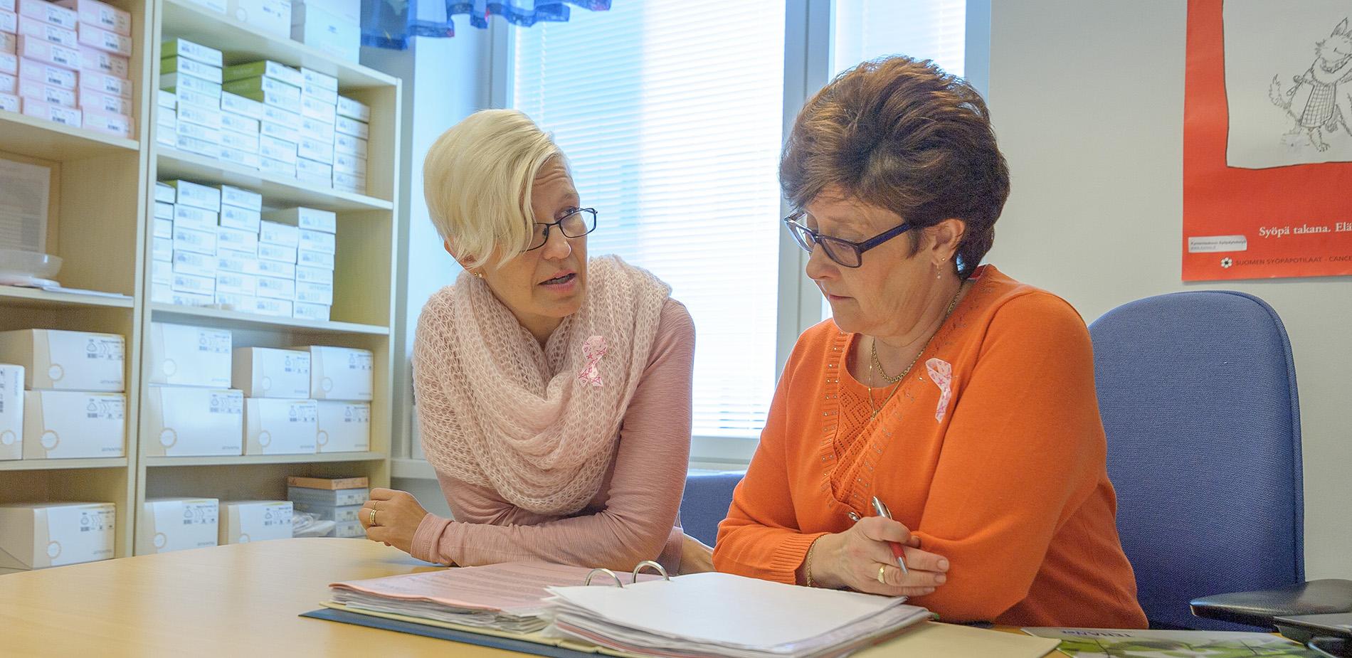 Sairaanhoitajaa keskustelevat pöydän ääressä syöpään liittyvistä asioista