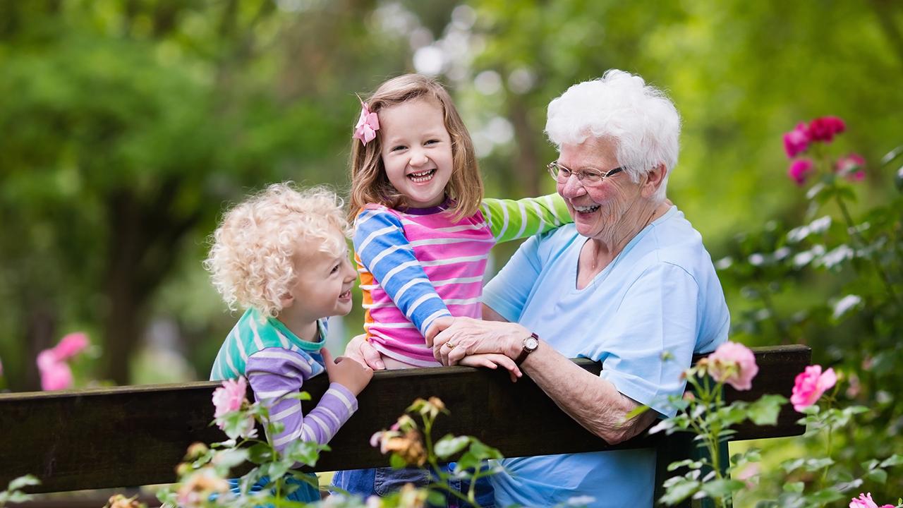 Isoäiti leikkii lastenlastensa kanssa puutarhassa.