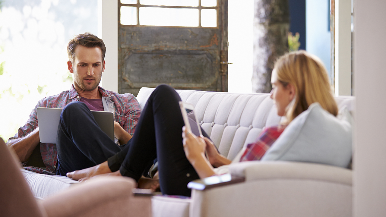 Pariskunta istuu sohvalla, molemmat tutkivat tietokoneidensa näyttöjä..