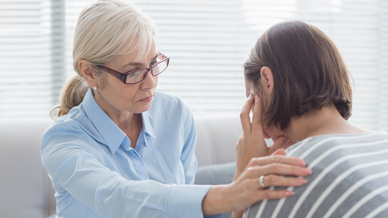 Hoitaja lohduttaa potilasta.