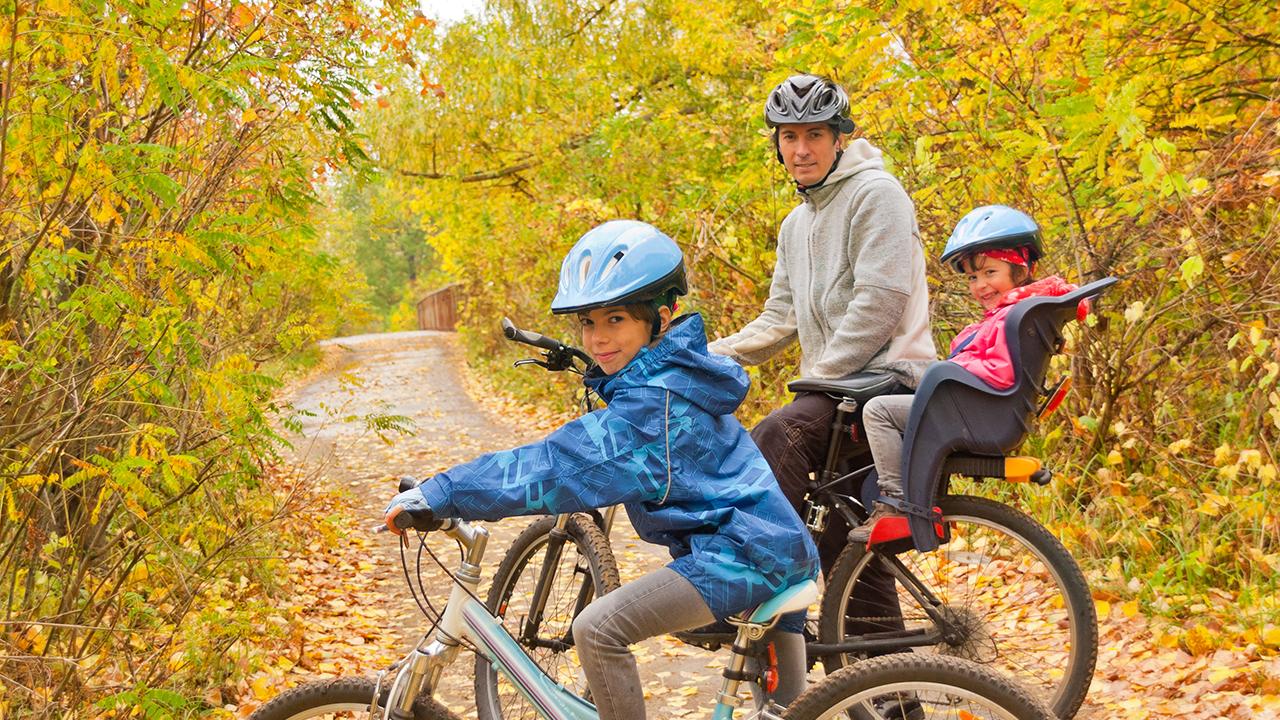 Isä pyöräilee lastensa kanssa