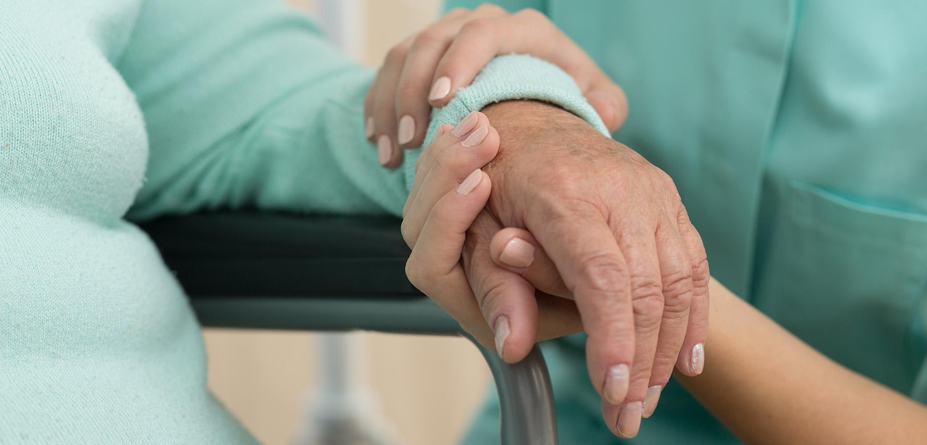 Hoitaja pitää potilasta kädsestä