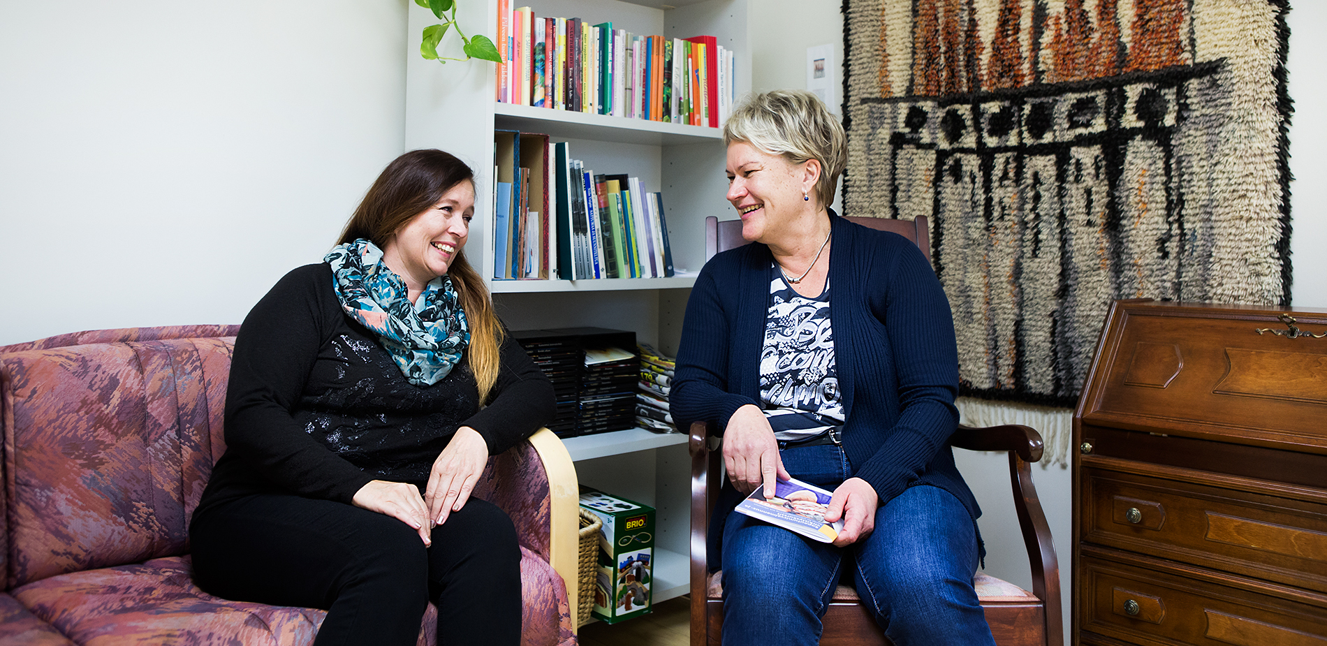 Kaksi naista istuu ja hymyilee toisilleen sohvalla ja keinutuolissa. He