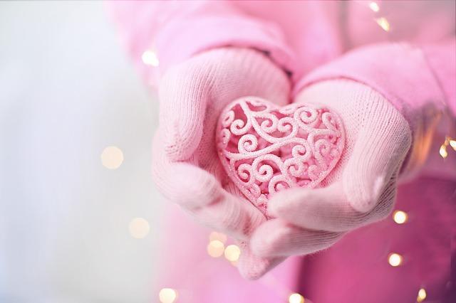 Kädet, joissa neuloshansikkaat ja sydänkoriste.