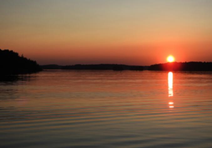 Auringonlasku järven yllä.
