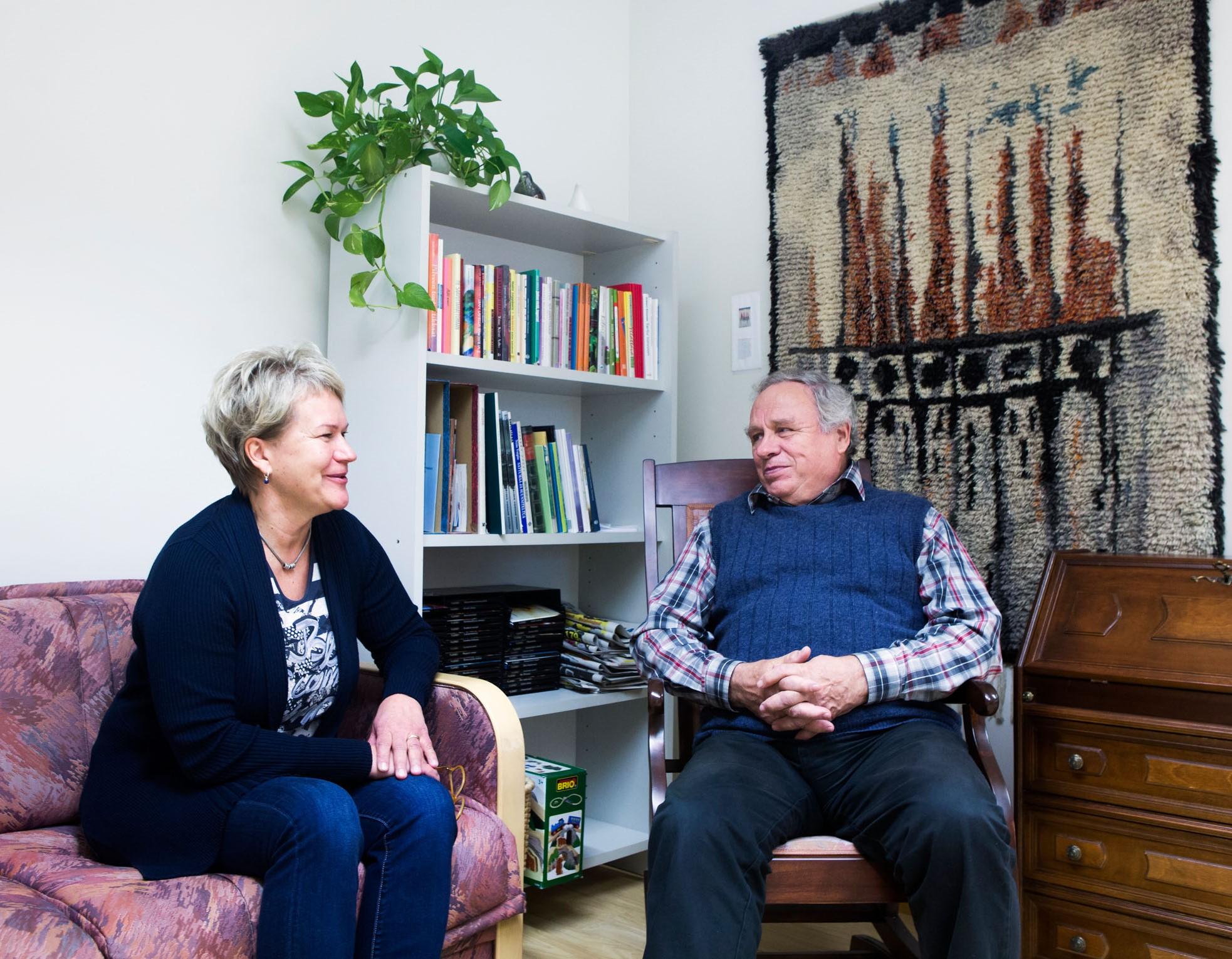 Nainen sohvalla ja mies keinutuolissa keskustelemassa.
