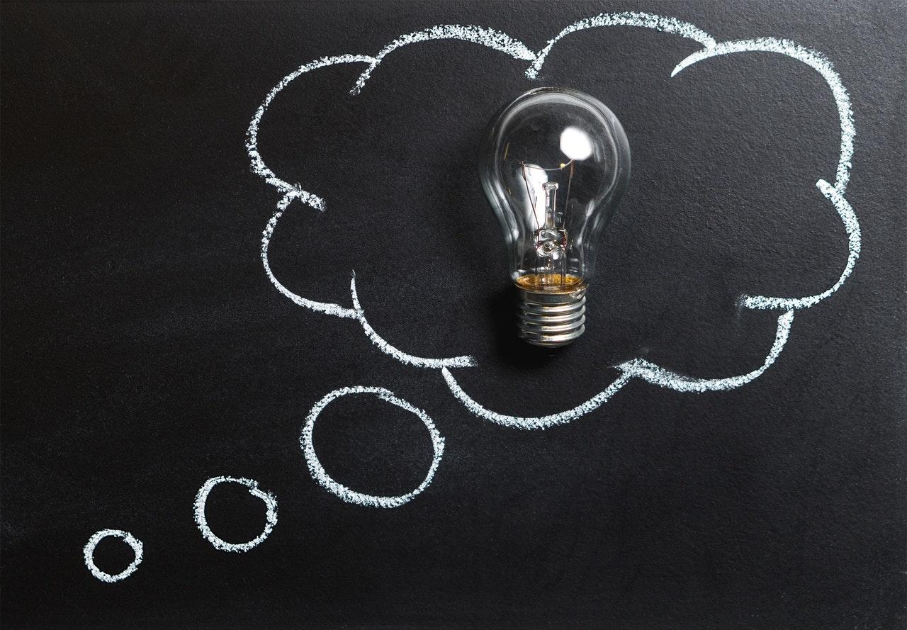 Liitutauluun piirretty ajatuskupla, jonka sisässä hehkulamppu