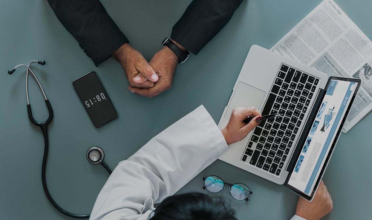 Lääkäri ja potilas tietokoneen äärellä