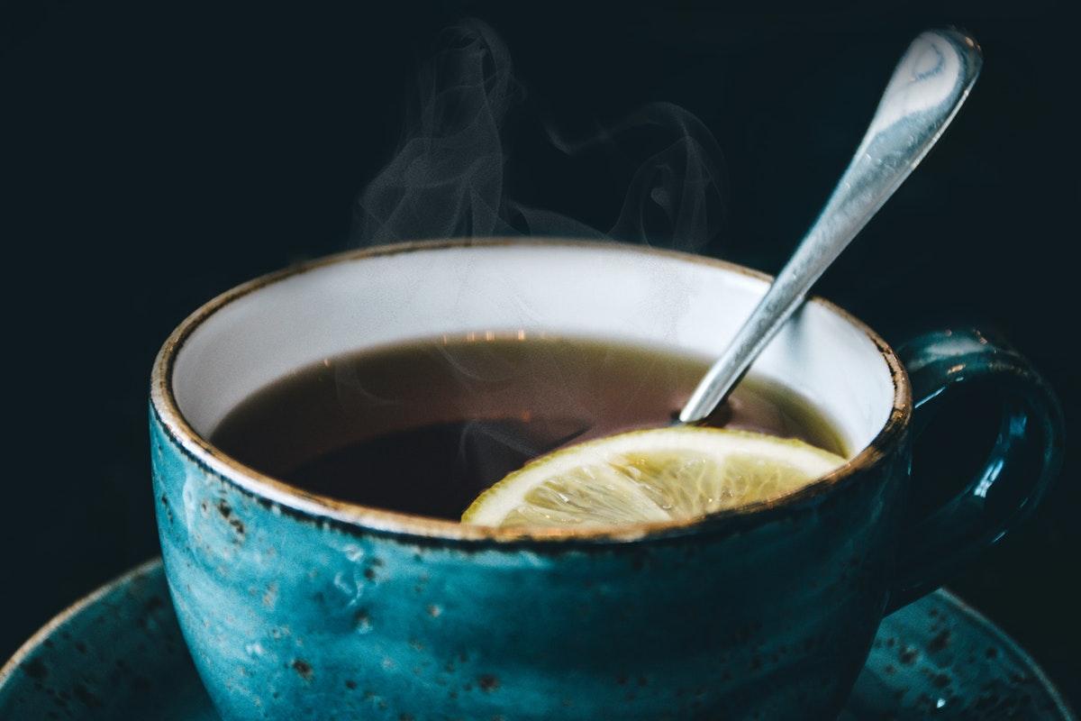 teetä sinisessä kupissa mustaa taustaa vasten