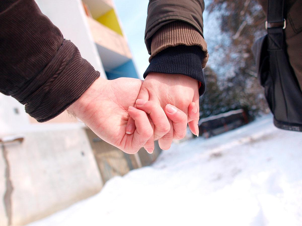 Kaksi ihmistä käsi kädessä ulkona