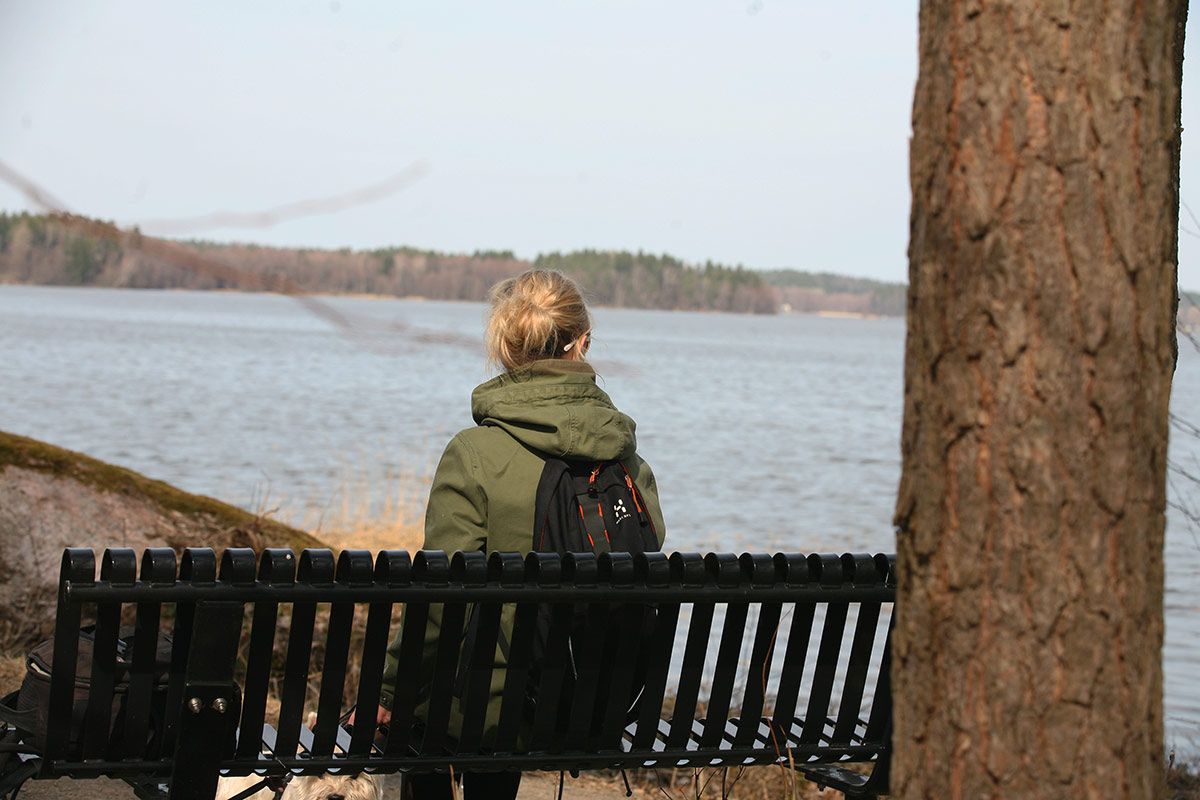 Nainen istuu penkillä veden äärellä