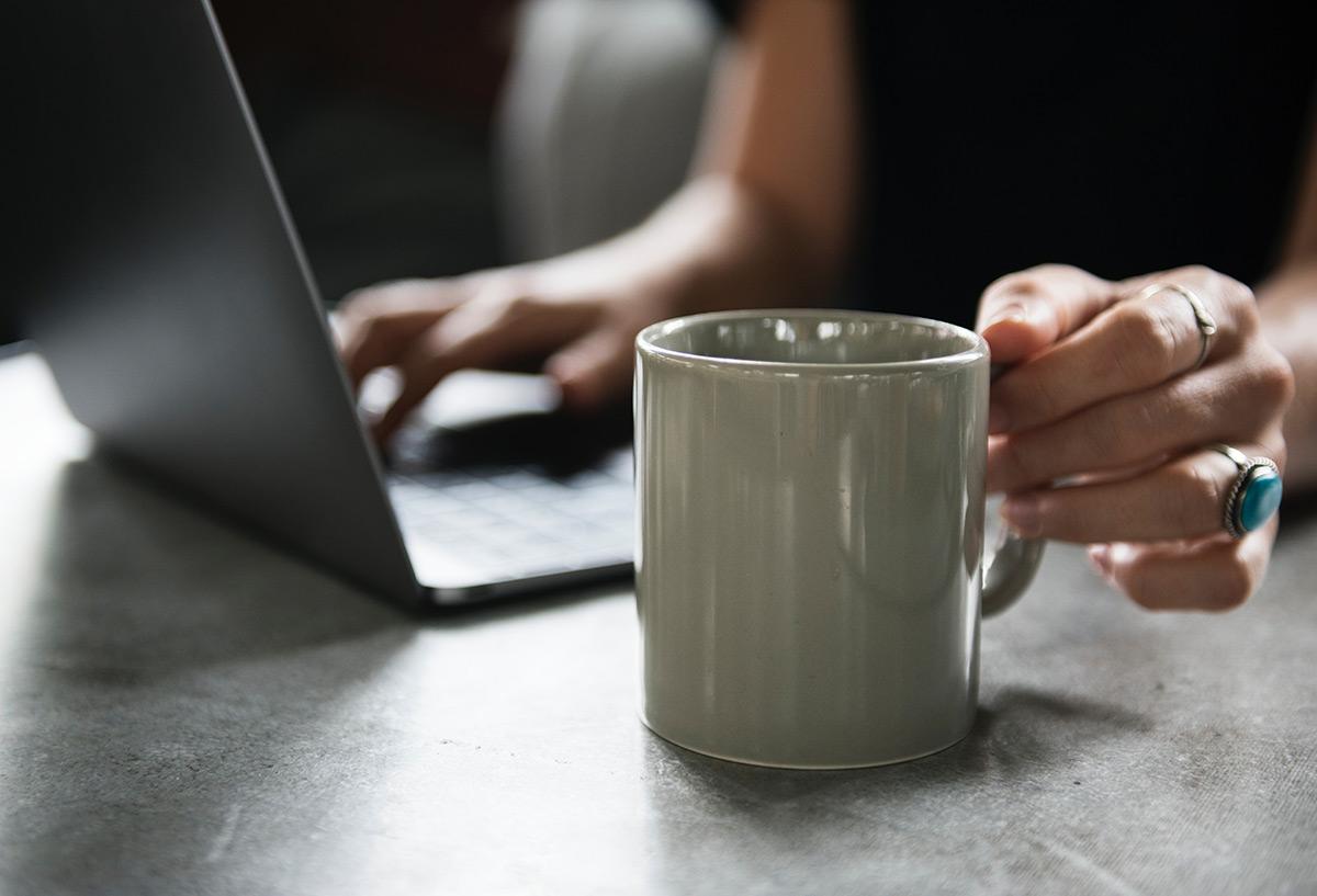 Kahvimuki ja kannettava tietokone, jonka ääressä ihminen