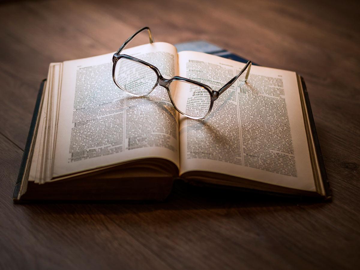 Avoin kirja pöydällä, silmälasit kirjan päällä
