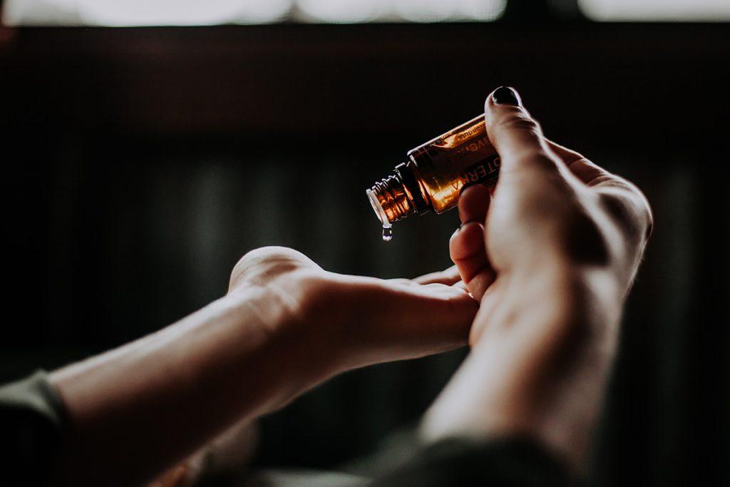 Ruskea lääkepullo ihmisen käsissä