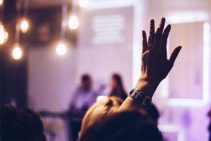 Ihminen viittaa saadakseen puheenvuoron seminaarissa