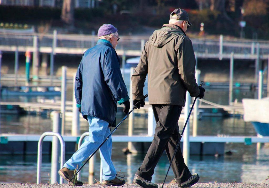 Kaksi vanhempaa miestä sauvakävelemässä