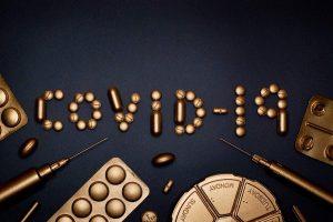 Teksti covid-19 pronssinvärisillä lääkkeillä kirjoitettuna