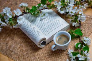 Kirja pöydällä omenanoksan alla, vieressä kahvikuppi