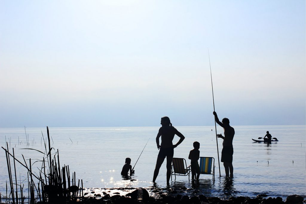 Perhe kalastaa rantavedessä