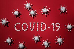 Covid-19 -teksti valkoisista pillereistä punaisella taustalla