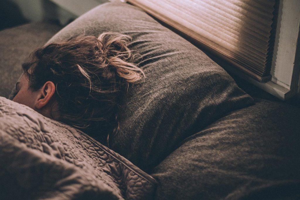Ihminen nukkuu sängyssä peiton alla
