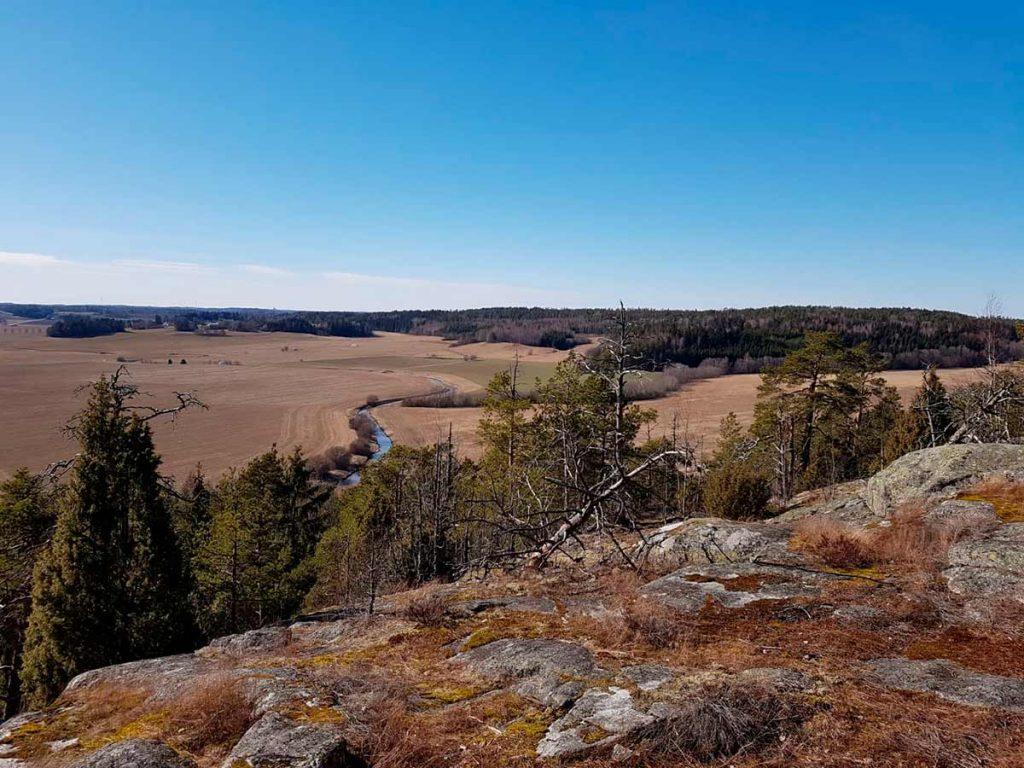 kalliolta kuvattu peltomaisema taustalla metsää