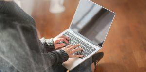 Nainen istuu lattialla kannettava tietokone sylissään