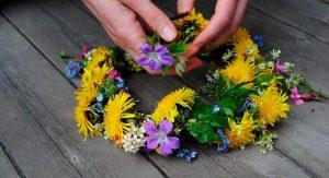 Kädet punomassa kukkaseppelettä luonnonkukista