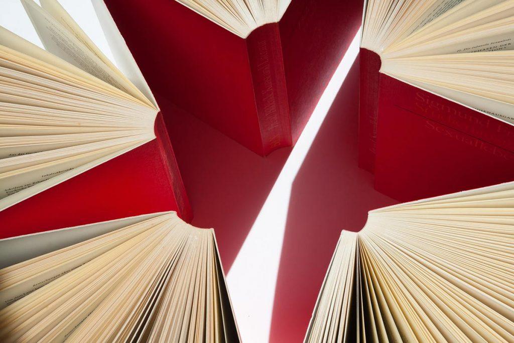 Punakantiset kirjat pystyssä pöydällä