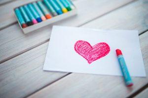 Pöydällä väriliidut ja kortti, johon piiretty punainen sydän