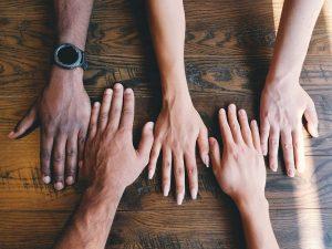 Ihmisten käsiä puisella pöydällä