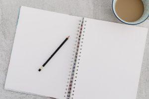 Muistikirja, kynä ja kuppi kahvia pöydällä