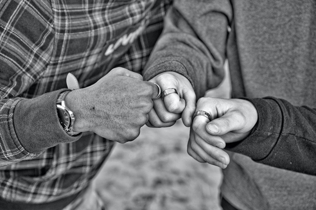 Mustavalkoinen kuva, kolme kättä nyrkissä, tuotu yhteen yhteistyön merkiksi