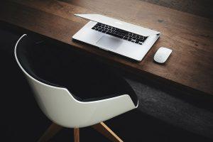 Työpöydällä kannettava tietokone ja hiiri, pöydän ääressä valkoinen tuoli