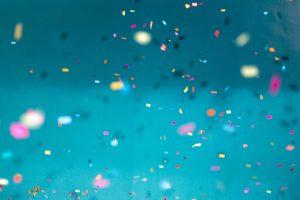 Värikästä konfettia leijailee ilmassa turkoosia taustaa vasten