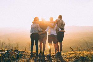 Kaverukset katsomassa auringonlaskua kädet toistensa olkapäillä