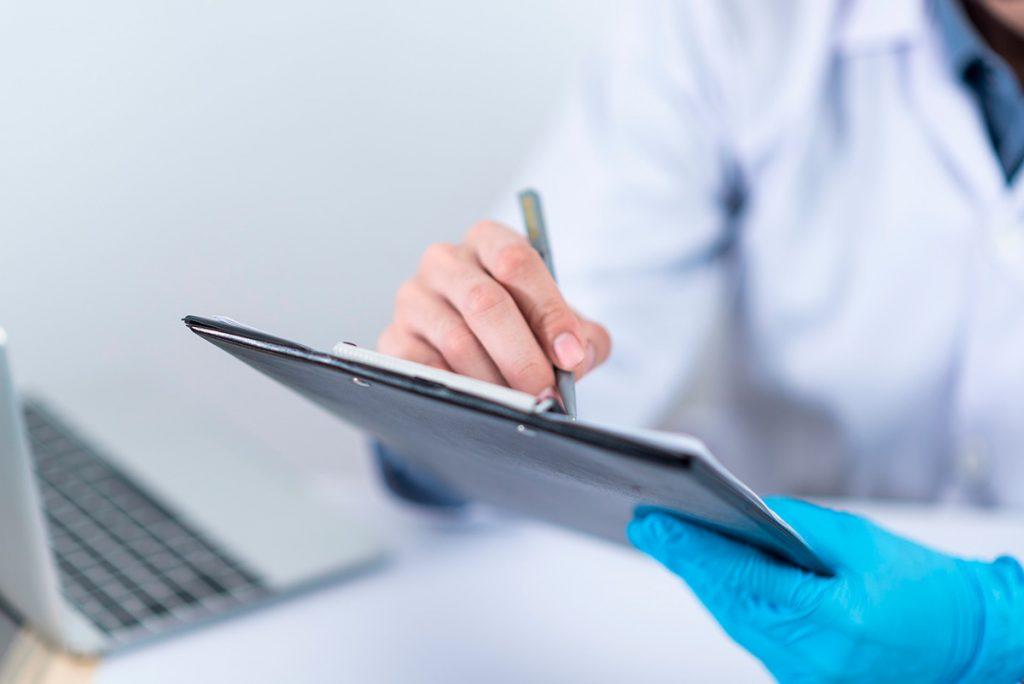 Lähikuva lääkäristä tekemässä muistiinpanoja paperiin