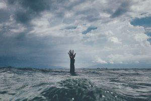 Käsi ojentuneena veden pinnan yläpuolella