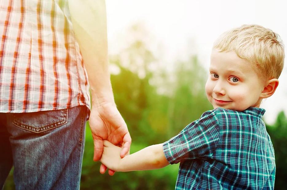 Isä ja poika kävelevät käsikädessä. Poika katsoo olkansa yli kohti kameraa.