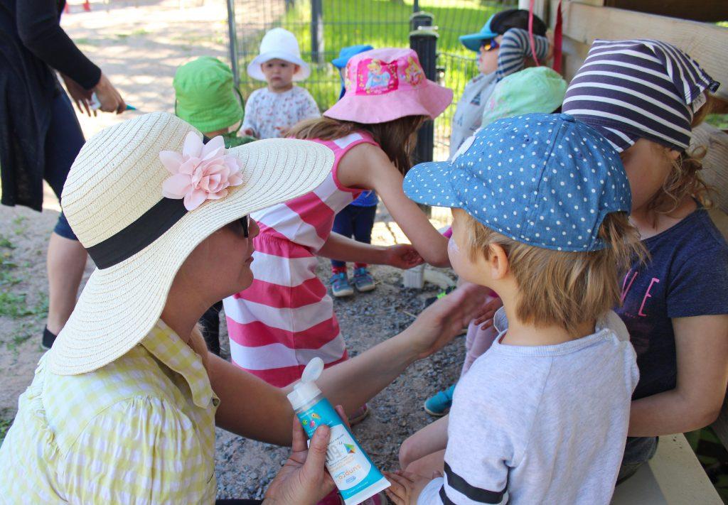 Aurinkoagentit opettavat päiväkodin lapsia levittämään aurinkorasvaa.