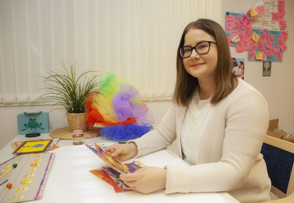 Lasten tunnetaito-ohjaaja Pia Ilves istuu työpöytänsä äärellä. Avaa kuva isompana.