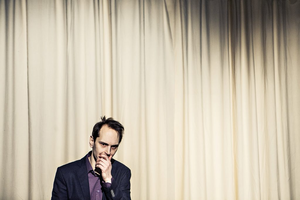Valokuva Joka neljäs -esityksestä. Kuvassa mies seisoo esiripun edessä.