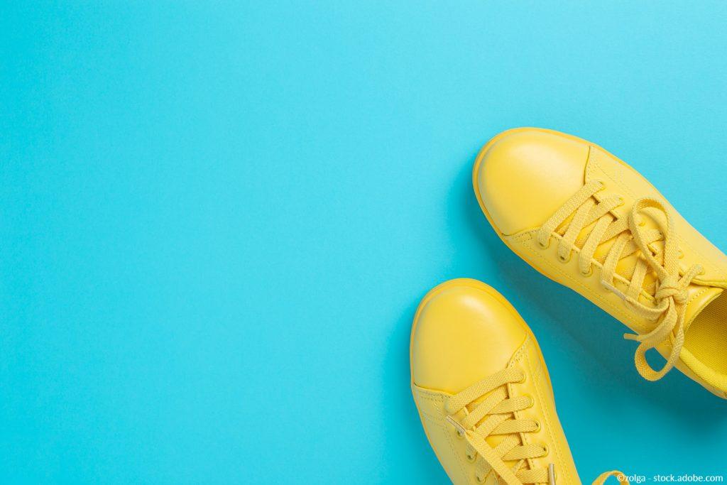 Kuvassa on kaksi keltaista kenkää turkoosilla lattialla.