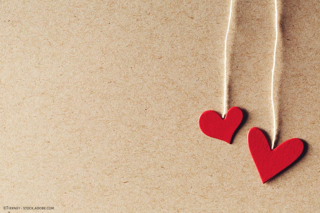 Kaksi käsintehtyä paperista sydänkoristetta on asetettu ruskean paperin päälle.