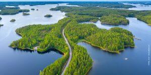 Kuva on ilmakuva, jossa on metsää, järveä ja tie.