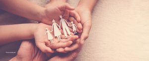 Lapsen ja vanhemmat kädet kannattelevat paperista leikattua perhettä.