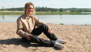 Kuvassa on NIKO-projektin kesätyöntekijä Artturi Laaksonen, joka istuu Meri-Karinan hyvinvointikeskuksen läheisyydessä sijaitsevan Sorttamäen hiekkarannalla.